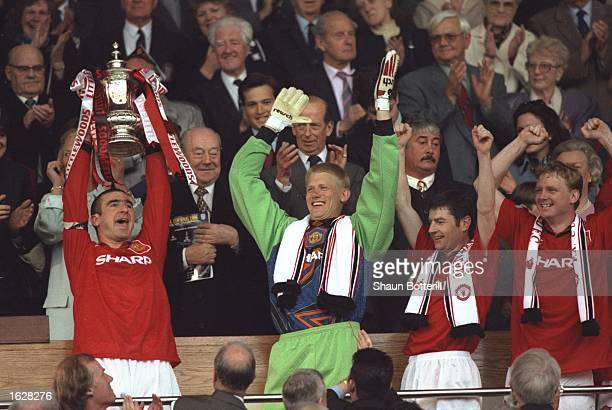 Eric Cantona of Manchester United holds aloft the trophy and Peter Schmeical Denis Irwin and David May all of Manchester United celebrate after...