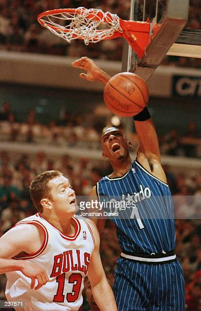 Forward Anfernee Hardaway of the Orlando Magic dunks the ball over Center Luc Longley of the Chicago Bulls during first quarter action of game one of...