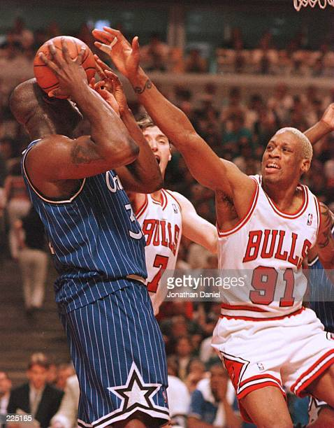 Forward Dennis Rodman of the Chicago Bulls defends against center Shaquille O''Neal of the Orlando Magic during the third quarter of game one of the...