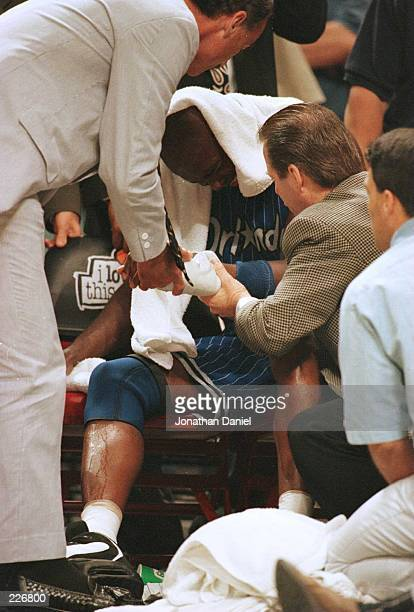 Forward Horace Grant of the Orlando Magic is examined by team doctors on the bench during the fourth quarter of game one of the Eastern Conference...