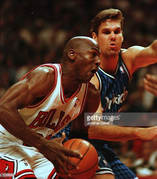 Guard Michael Jordan drives to the basket past forward Jon Koncak of the Orlando Magic during the third quarter of action in game two of the NBA...