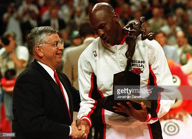 Guard Michael Jordan of the Chicago Bulls shakes hands with NBA Commissioner David Stern as he is presented with the 1996 NBA Most Valuable Player...