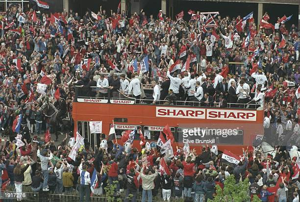 The Manchester United team stand on the top deck of a bus surrounded by supporters as they parade through their home town after winning the FA Cup...