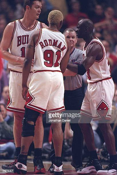 Center Luc Longley forward Dennis Rodman and guard Michael Jordan of the Chicago Bulls talk to referee Joe Crawford during a playoff game against the...