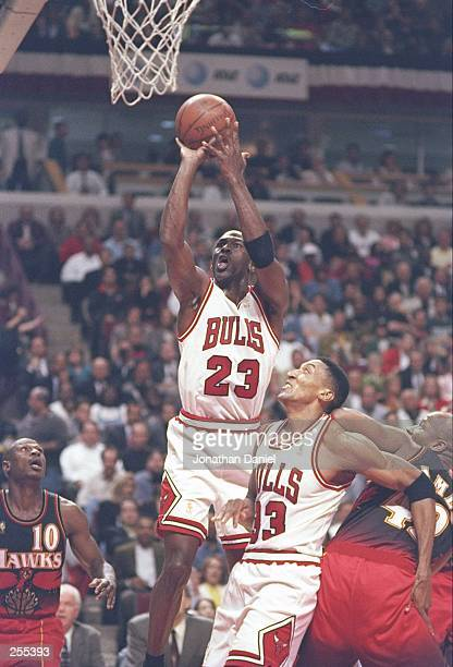 Guard Michael Jordan of the Chicago Bulls shoots the ball as Henry James and guard Mookie Blaylock of the Atlanta Hawks and forward Scottie Pippen of...