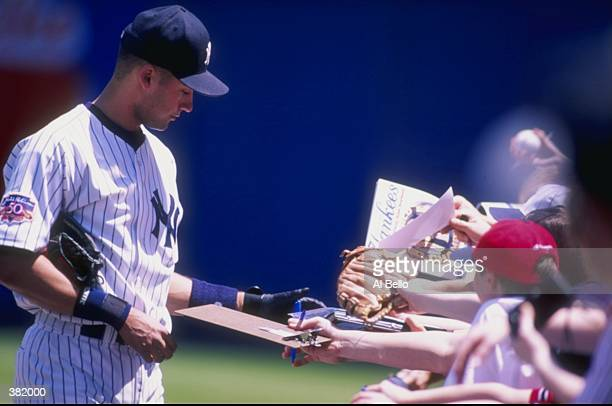 Infielder Derek Jeter of the New York Yankees signs autographs during a game against the Boston Red Sox at Yankee Stadium in New York City, New York....