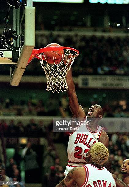 Michael Jordan of the Chicago Bulls dunks the ball as Dennis Rodman watches during the game against the Miami Heat at the United Center in Chicago...