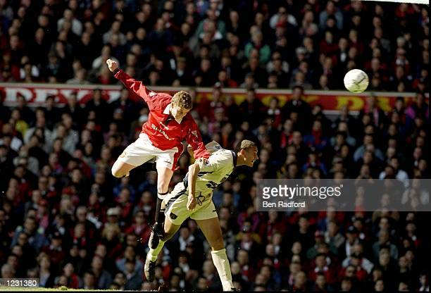 Ole Gunnar Solskjaer of Manchester United and Rio Ferdinand of West Ham United jump for the ball during an FA Carling Premiership match at Old...