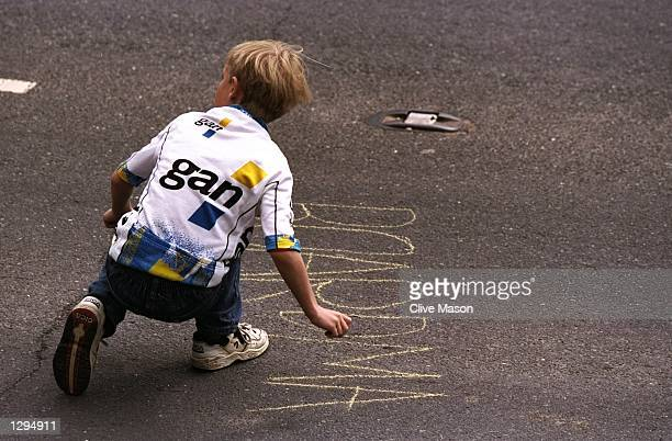 A young fan writes the name of Chris Boardman of Great Britain on the road during the Fifth Stage of the Prutour 98 Around Britain Cycle Race between...