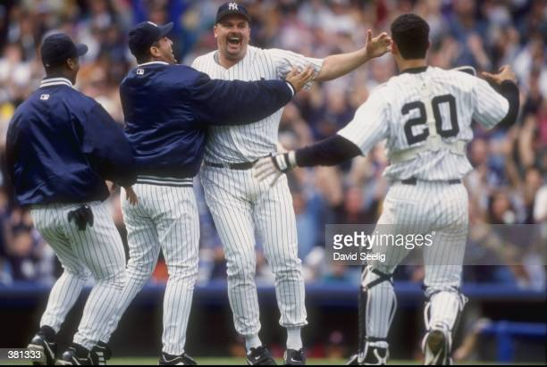 David Wells of the New York Yankees celebrates his perfect game against the Minnesota Twins with teammates Jorge Posada and Luis Sojo at Yankee...