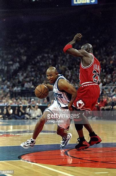 David Wesley of the Charlotte Hornets dribbles the ball as Michael Jordan of the Chicago Bulls block during the East Conference Semifinals at...