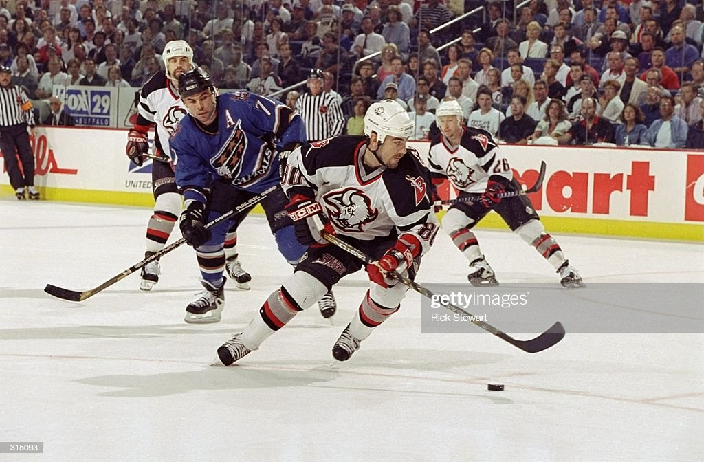 Geoff Sanderson #80 of the Buffalo Sabres is pursued by Adam Oates #77 of the Washington Capitals during an Eastern Conference Finals playoff game at the Marine Midland Arena in Buffalo, New York. The Capitals defeated the Sabres 4-3.