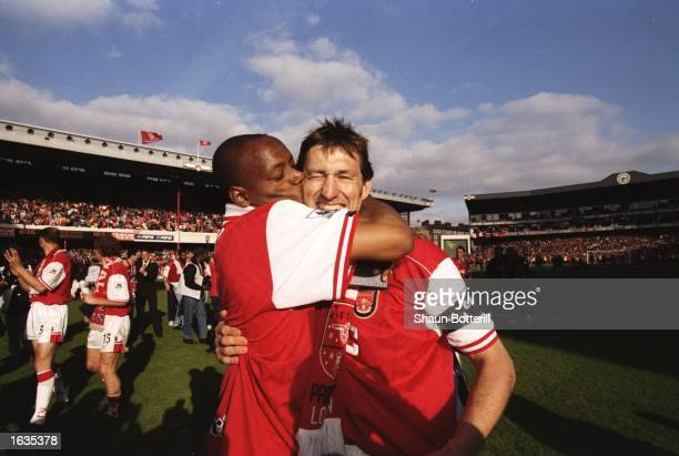 Ian Wright of Arsenal kisses his captain Tony Adams after winning the championship in the FA Carling Premiership match against Everton at Highbury in...