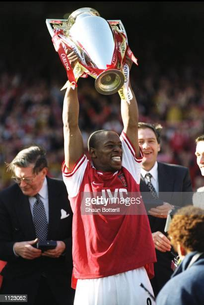 Ian Wright of Arsenal proudly lifts the championship trophy after the FA Carling Premiership match against Everton at Highbury in London Arsenal won...