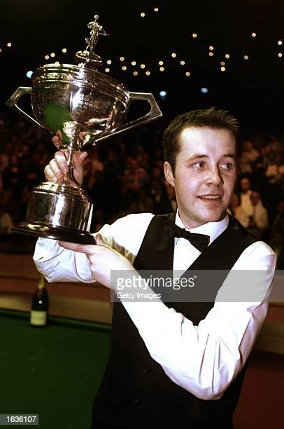 John Higgins of Scotland raises the trophy aloft after winning the World Snooker Championship final against Ken Doherty of the Republic of Ireland at...