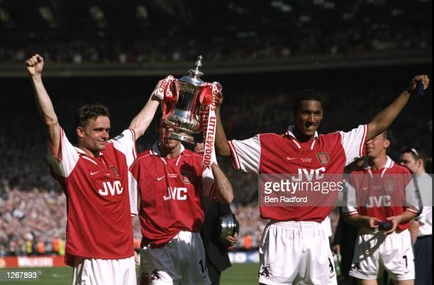 Marc Overmars and Nicolas Anelka of Arsenal hold the trophy aloft after the FA Cup final against Newcastle United at Wembley Stadium in London...