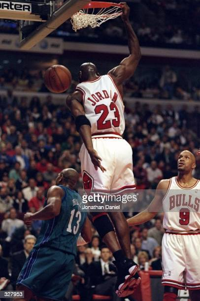 Michael Jordan and Ron Harper of the Chicago Bulls in action against Bobby Philis of the Charlotte Hornets during the NBA Playoffs round 1 game at...