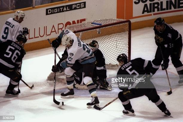 Murray Craven of the San Jose Sharks looks for an open shot around goaltender Ed Belfour of the Dallas Stars during the Sharks 3-2 loss at San Jose...