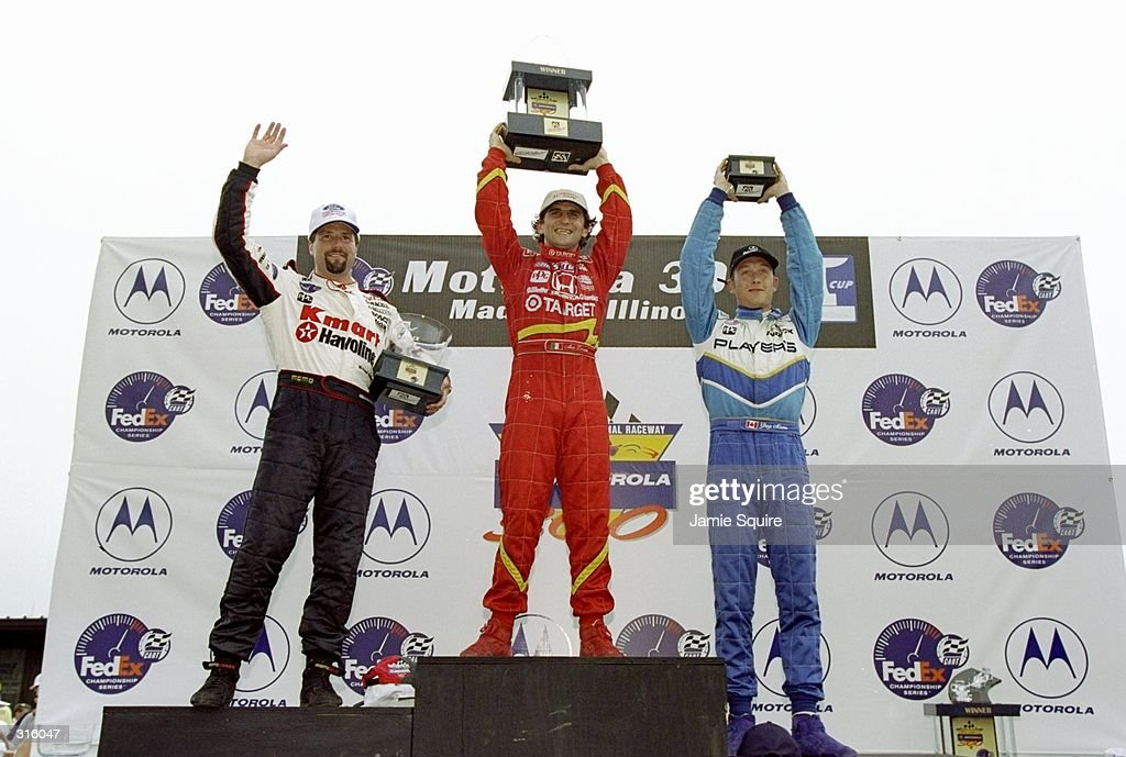 Winner Alex Zanardi (c), second-placed Michael Andretti (L) and third-placed Greg Moore R) hoist their trophies on the podium after the CART Motorola 300 at the Gateway International Raceway in Madison, Illinois.