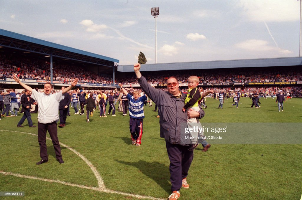 09 May 1999 - English Football League Division One - Queens Park Rangers (QPR) v Crystal Palace - QPR fans on the pitch celebrating promotion to the Premiership and taunting the Palace supporters, including one man carrying a small child.