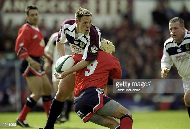 Mark Taylor of Llanelli is tackled by Rupert Moon during the SWALEC Cup Final clash between Llanelli and Swansea, played at Ninian Park, Cardiff,...