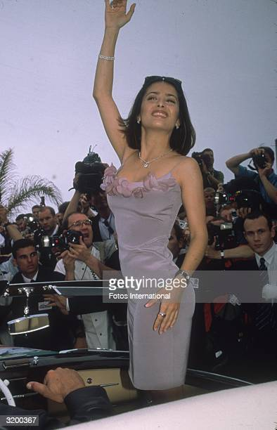 Mexican actress Salma Hayek wearing a lavender dress standing in a car and waving to photographers at the Cannes International Film Festival Cannes...