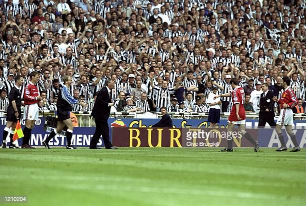 Newcastle fans celebrate as Roy Keane of Manchester United is substituted off the field due to injury during the AXA FA Cup Final match against...