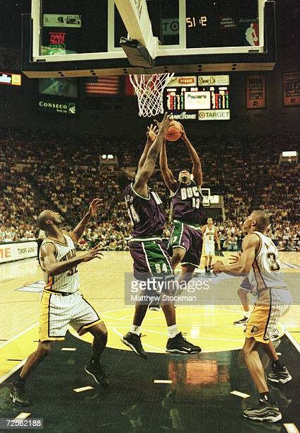 Robert Traylor and Glenn Robinson of the Milwaukee Bucks battle for a rebound against Dale Davis and Antonio Davis of the Indiana Pacers during game...