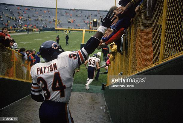 Walter Payton of the Chicago Bears shakes hands with fans before a game against the Green Bay Packers in Green Bay, Wisconsin.