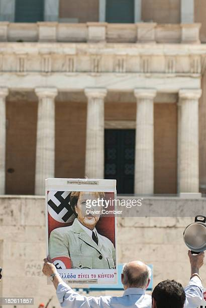 CONTENT] May 1st demonstration in Athens in front of the Greek parliament A panel with Angela Merkel wearing mustache and suit Adolf Hilter is...