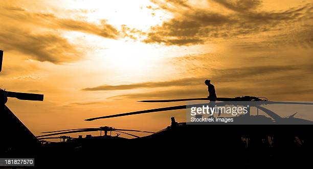 May 2, 2012 - A pilot conducts a pre-flight inspection on a UH-60 Black Hawk helicopter as the sun rises.