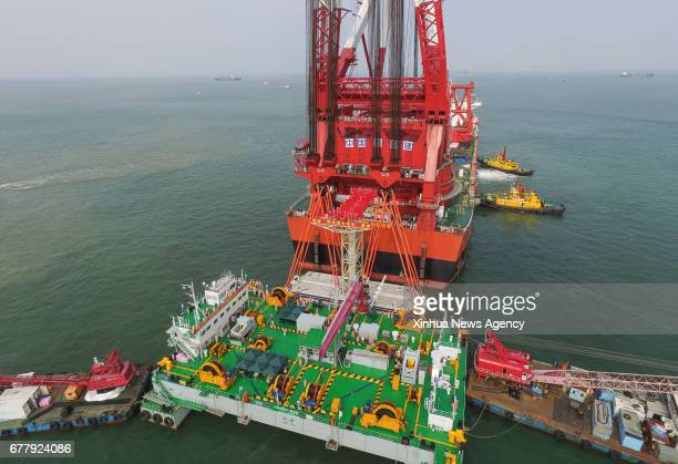 ZHUHAI May 2 2017 A gigantic crane which was transformed from a tanker hoists a 6000ton key structure of the world's longest crosssea bridge linking...