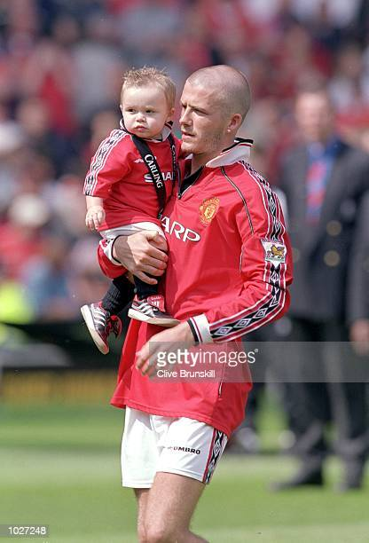 David Beckham of Manchester United celebrates winning the championship with son Brooklyn after the FA Carling Premiership match against Tottenham...