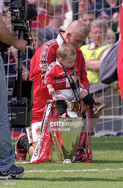 David Beckham of Manchester United sits son Brooklyn on the championship trophy after the FA Carling Premiership match against Tottenham Hotspur at...