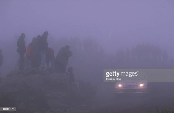 Francois Delecour of France in his Peugeot 206 appears through the mist during the sixth round of the World Rally Championships in Argentina Picture...