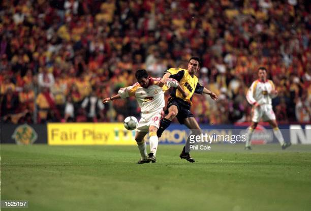 Gheorghe Hagi of Galatasaray holds off a challenge from Marc Overmars of Arsenal during the UEFA Cup final at the Parken Stadium in Copenhagen...