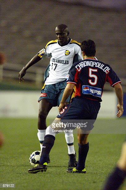 Ezra Hendrickson of the Los Angeles Galaxy dribbles against the defense of the New England Revolution at the Rose Bowl in Pasadena, California. The...