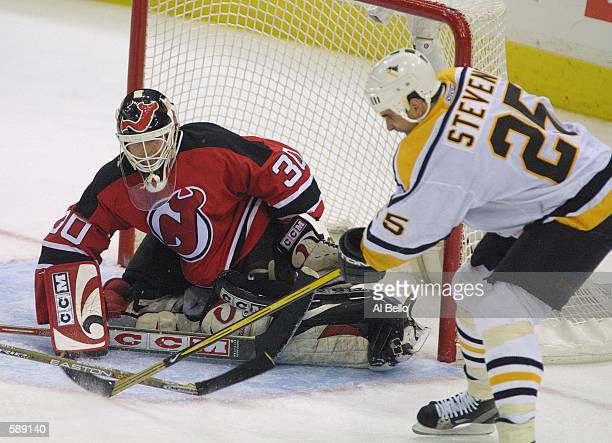 Martin Brodeur of the New Jersey Devils makes a save against Kevin Stevens of the Pittsburgh Penguins during the 3rd period of game 4 of their...