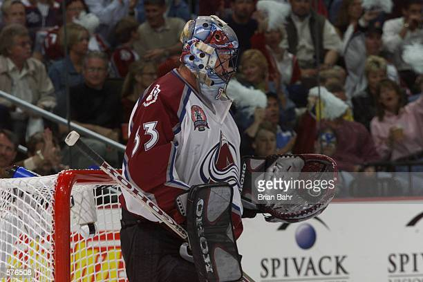 Patrick Roy of the Colorado Avalanche looks at the puck in his glove after making a save against the New Jersey Devils during the third period of...