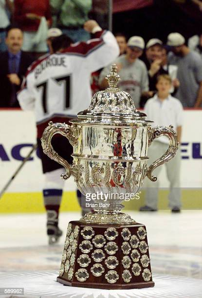 Ray Bourque of the Colorado Avalanche pumps his fist in the background as he leaves the ice behind the Western Conference Clarence Campbell Trophy...