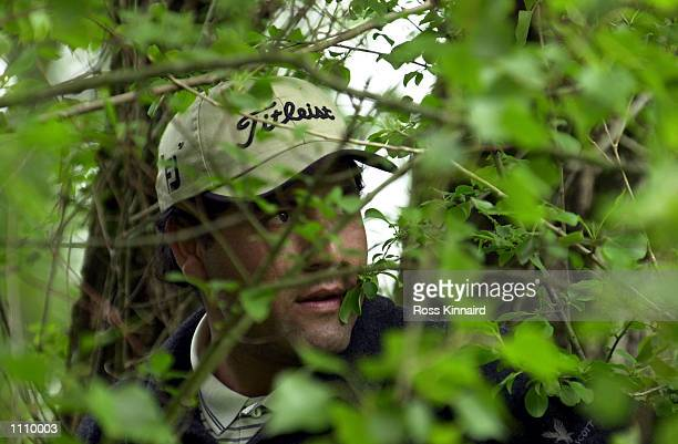 Ricardo Gonzalez of Argentina looks out from the trees on the 13th hole during his second round of the Novotel Perrier Open de France at the Golf...