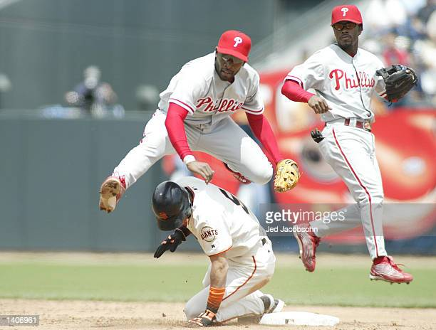 Marlon Anderson of Philadelphia Phillies jumps over Tsuyoshi Shinjo of the San Francisco Giants as Jimmy Rollins of the Phillies looks on at Pac Bell...