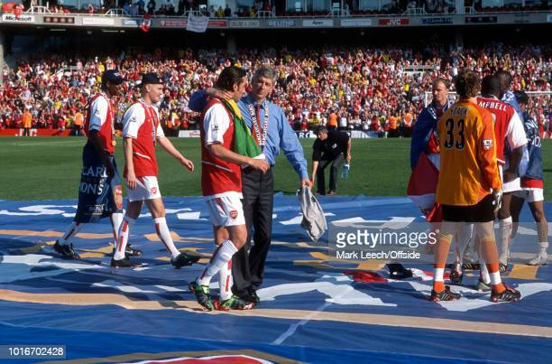 15 May 2004 Premiership Football Arsenal v Leicester City Arsenal manager Arsene Wenger puts his arm around Edu as they walk across a large...