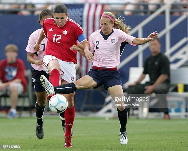 Canada's Christine Sinclair and United States defender Heather Mitts challenge for the ball Mitts' plant leg was injured on the play and she had to...