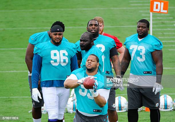 Miami Dolphins Defensive Tackle Ndamukong Suh catches the ball as Miami Dolphins Defensive Tackle AJ Francis Miami Dolphins Defensive Tackle Anthony...
