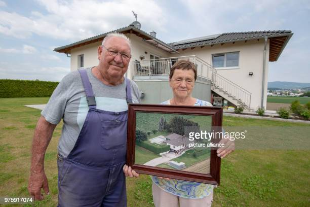 Rosemarie and Dietmar Seidler hold in front of their newly built house in Deggendorfer district fishing village a photo of their 2013 destroyed in...