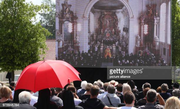 People watch the funeral on a screen Photo Thomas Warnack/dpa