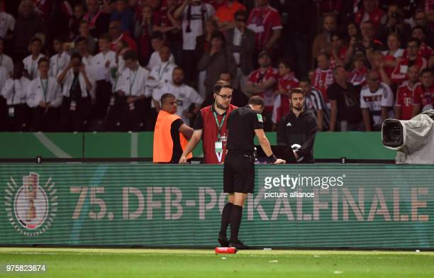 Football German DFB Cup final FC Bayern Munich vs Eintracht Frankfurt at the Olympic Stadium Referee Felix Zwayer watches a video replay on a monitor...