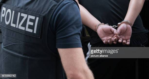German police officers walk off an arrested man on the ErichKurzStrasse during a largesccale raid against a gang of suspected human traffickers About...