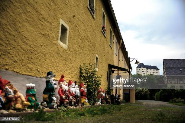 May 2018, Germany, Burgk: Garden gnoes standing at the side of a house in the valley of the Burgk castle. The castle was built in the middle ages....